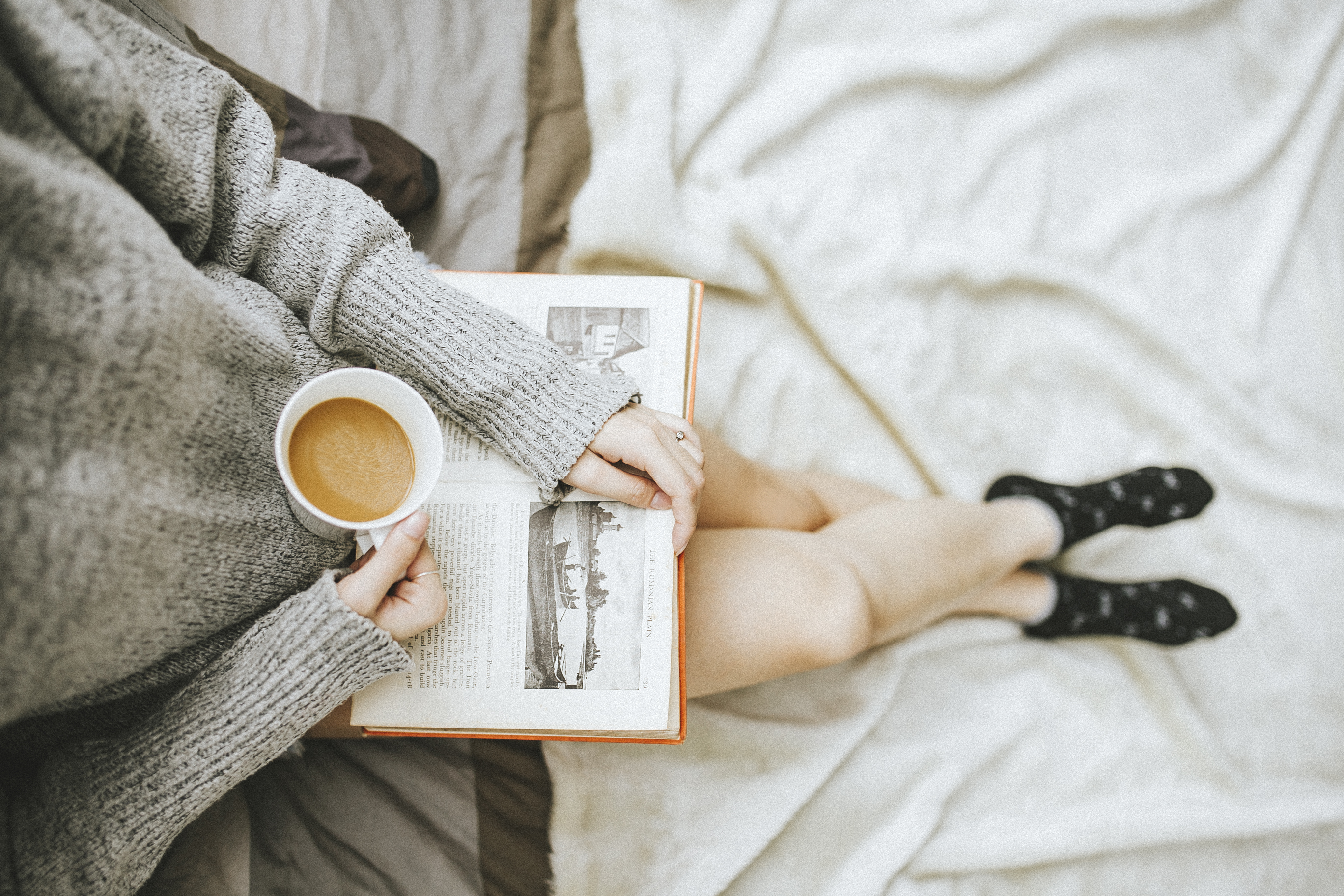 Image of a girl holding a cup of coffee with a book on her lap