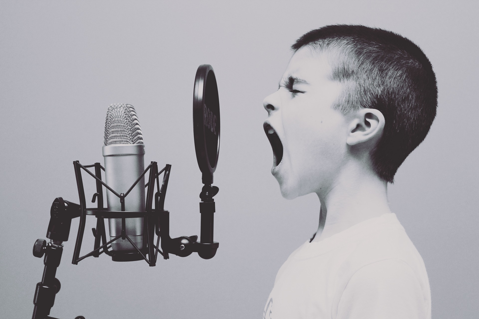 A boy is screaming into a microphone